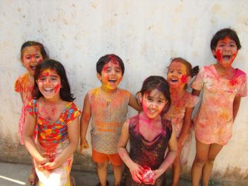 Mit leuchtend bunt gefärbtem Puder bestreute Kinder zum Frühlingsfest Holi