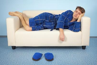 Mann in Bademantel auf Couch liegend