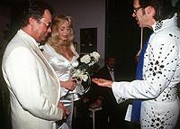 """Aus der Hand ihres Standesbeamten """"Elvis"""" nehmen Dolly Buster und Dino Baumberger während der Trauung in Las Vegas am 12.3.1997 die Eheringe entgegen."""