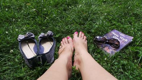 Blick auf bloße Füße, Schuhe und Reiseführer im Gras