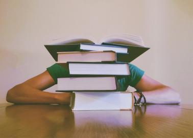 Gestresster Student vor Bücherhaufen