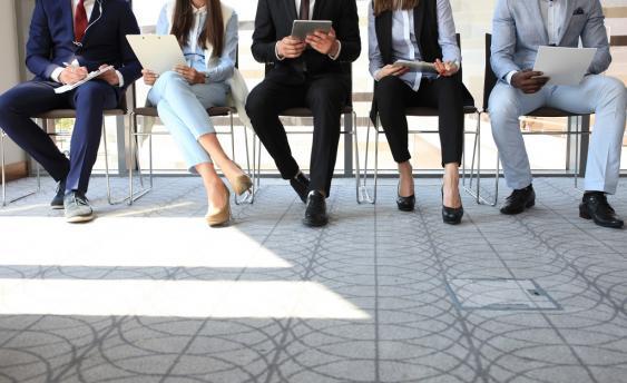 Fünf Sitzende Personen mit diversen Mobilgeräten und Akten