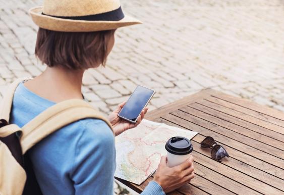 Touristin mit Stadtplan und Smartphone