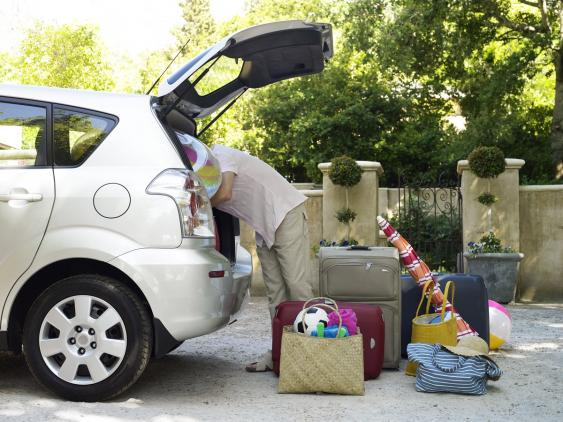 Mann zwischen Gepäckstücken vor geöffneter Heckklappe an Autos stehend