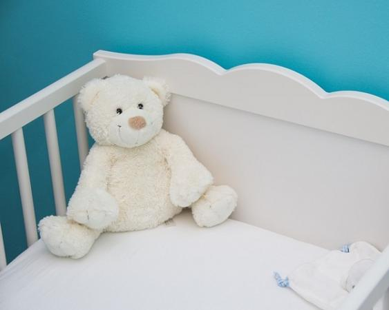 Kinderbett mit sitzendem Teddy