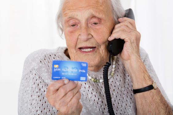 Seniorin mit Telefon und Kreditkarte