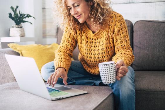 Frau mit Laptop und Tee