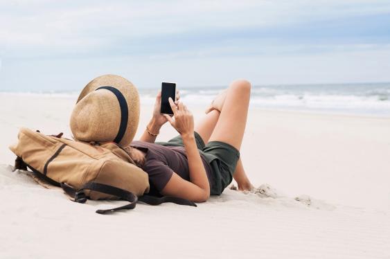 Junge Frau mit Smartphone an sonnigem Strand