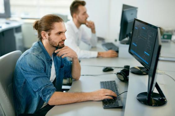 Junger Mann an Bildschirmarbeitsplatz