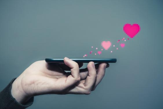 Smartphone mit aus dem Screen aufsteigenden gepixelten Herzchen