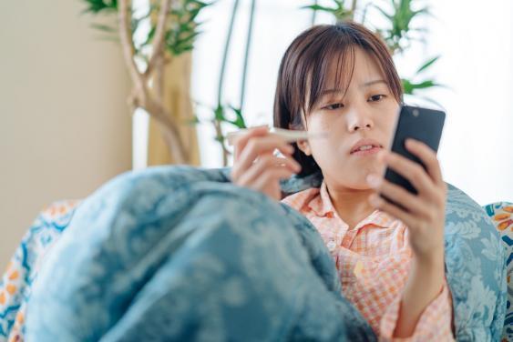 Junge Frau mit Smartphone bei Internetrecherche über Krankheitssymptome