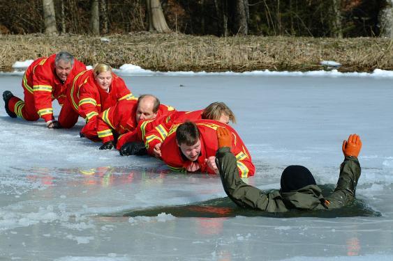 Lebensretter der DLRG halten sich auf dem Bauch liegend gegenseitig fest, um sich auf einer Eisfläche zu sichern.