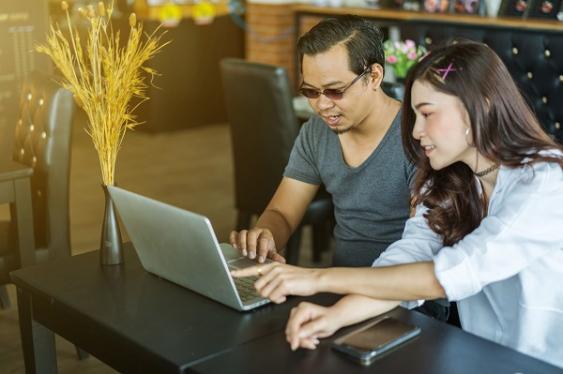 Chinesisches Paar vor einem Laptop