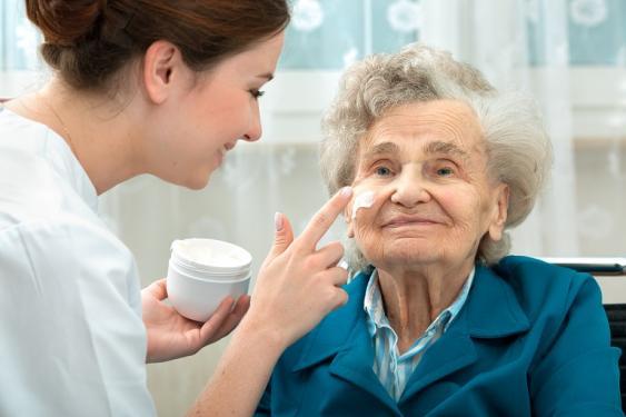 Pflegerin beim Auftragen einer Gesichtscreme