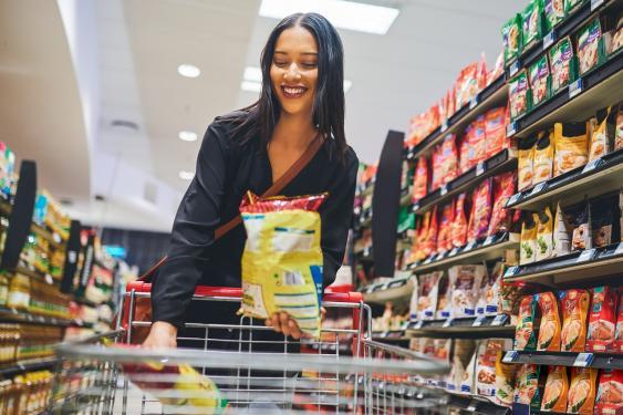 Junge Frau im Supermarkt beim Kauf von Snacks
