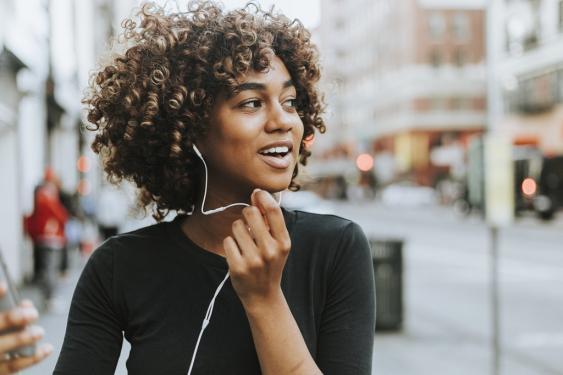 Junge Frau beim Telefonieren über Freisprechanlage