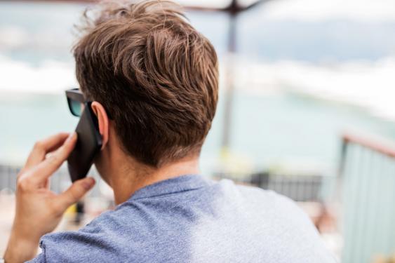 Junger MAnn mit Handy am Ohr, Rückansicht