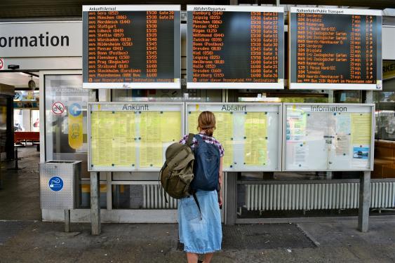 Frau vor Fahrplänen eines Busbahnhofs