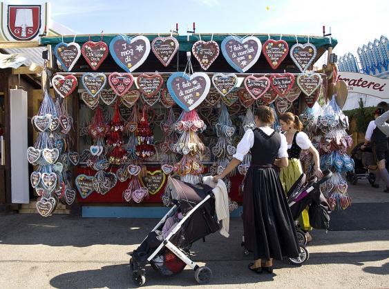 Trachtenträgerinnen mit Kinderwagen vor Herzlstand