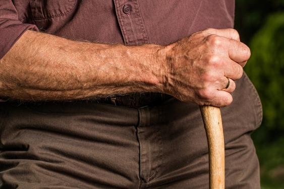 Hand eines alten Mannes mit gepackten Spazierstock