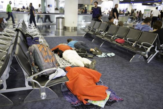 Auf dem Boden schlafende Personen in einer Flughafenwartezone