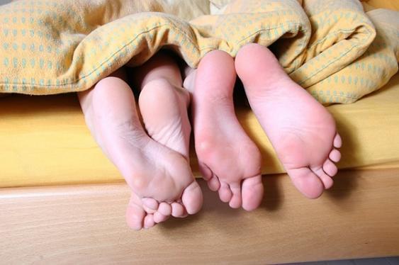 Unter einer Bettdecke hervorragende Füsse
