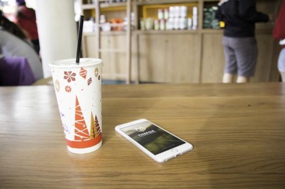 Abgelegtes Smartphone neben Pappbecher