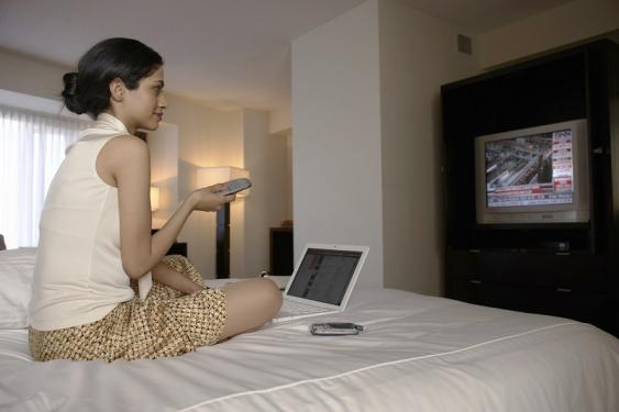 Frau in Hotelzimmer mit TV und Laptop