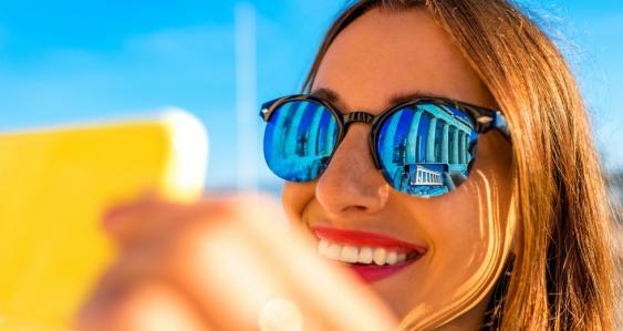 Junge Frau mit Sonnenbrille und Smartphone