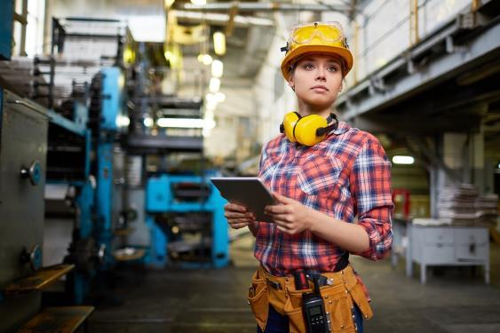 Junge Technikerin in Werkshalle