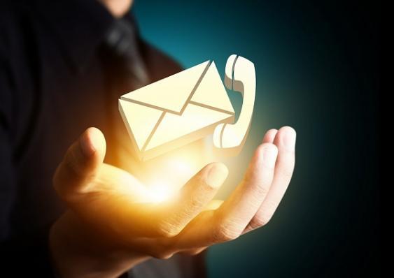Leuchtende, über einer Handfläche schwebende Postfach- und Telefon-Icons