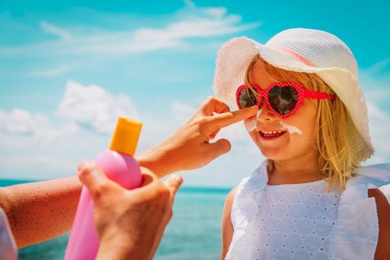Mädchen mit Sonnenbrille und -hut beim Eincremen mit Sonnenschutzcreme