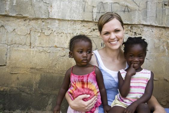 Junge, weiße Frau mit zwei afrikanischen Kindern