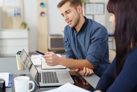 Zwei Büroangestellte im Gespräch an Laptop