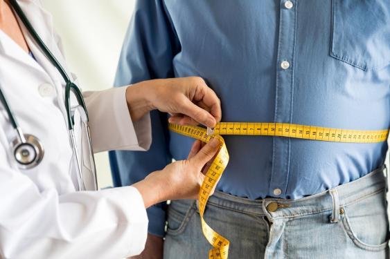 Ärztin bei der Messung des Bauchumfangs eines Patienten