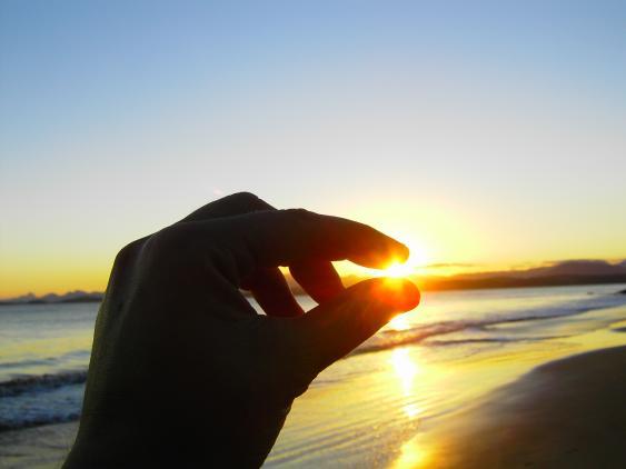 Untergehende Sonne zwischen Daumen und Zeiger