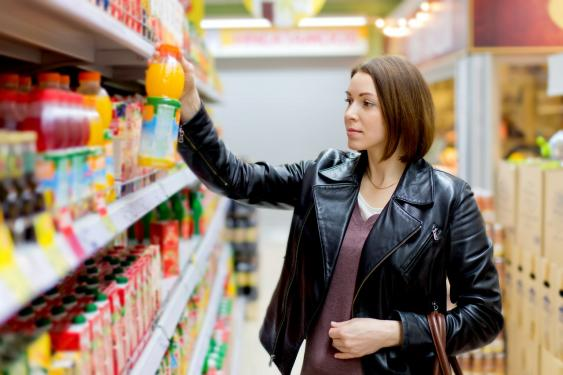 Frau vor Saftregal im Supermarkt