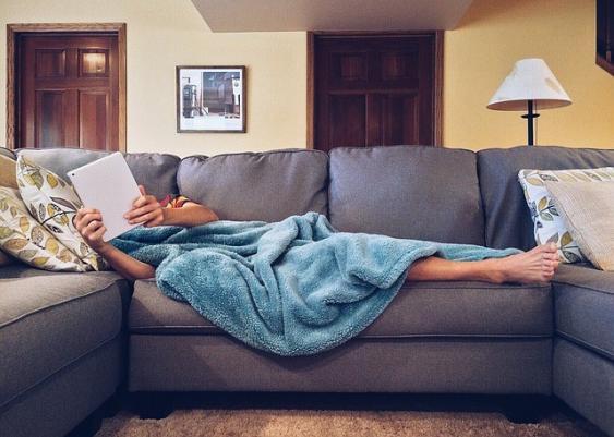 Auf einer Couch liegender Mann beim anschauen eines auf einem Tablet laufenden Films