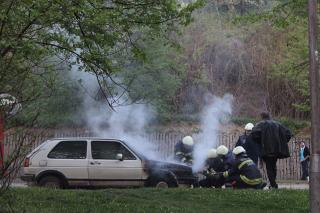 Feurwehrleute neben ausgebranntem Fahrzeug