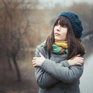 Frierende junge Frau im Freien