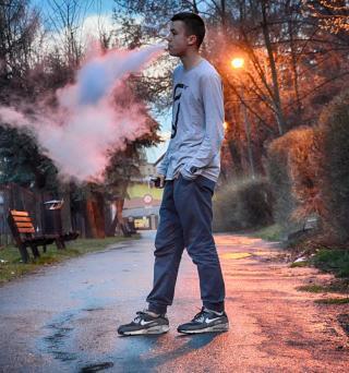 Junger Raucher mit E-Zigarette