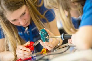 Zwei Mädchen bearbeiten ein LED Licht mit einer Zange
