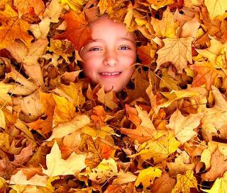 Kindergesicht schaut aus Blätterhaufen hervor