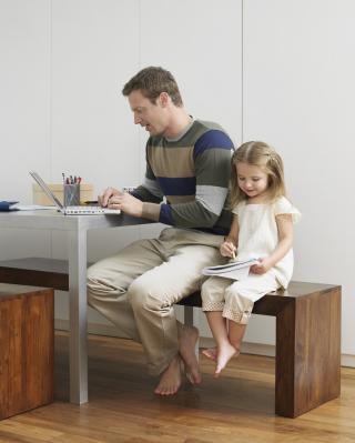 Arbeitender Vater mit Tochter