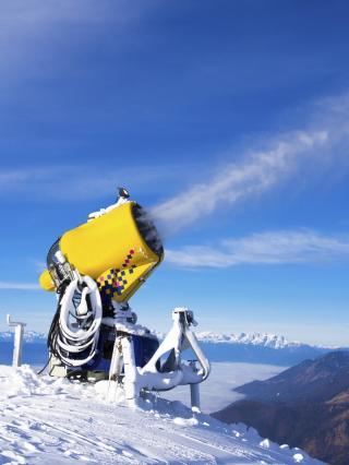 mobiel Schneekanone in verschneiter Alpenlandschaft