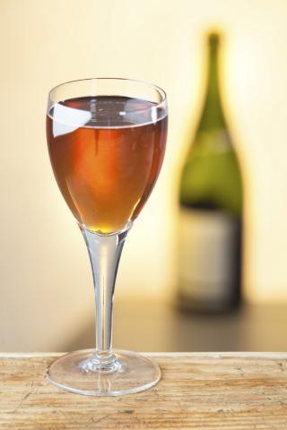 Weinglas mit Orange Wine, Flasche im Hintergrund sichtbar