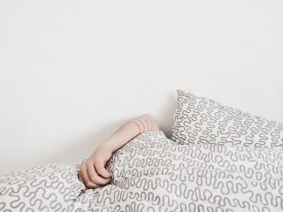 Zwischen Kopfkissen und Bettdecke hervorschauender Arm