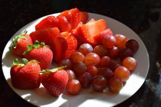 Teller mit Erdbeeren und Weintrauben