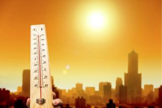 Thermometer vor hitzegeplagter Stadt