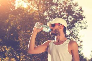 Trinkender Jogger mit weißer Kappe